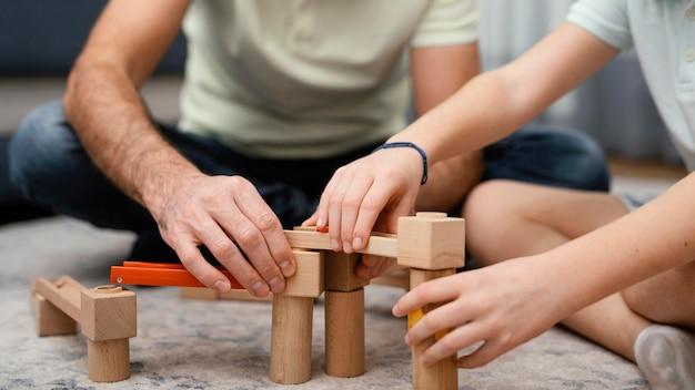Pai e filho brincando com brinquedos, vista frontal