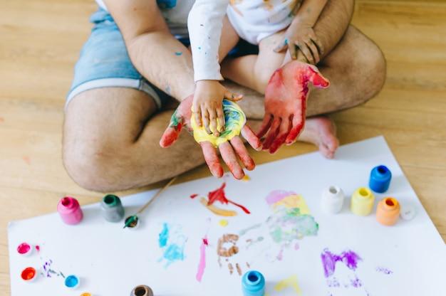 Pai e filho brincando com cores de tinta