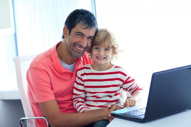 Pai e filho brincando com um laptop