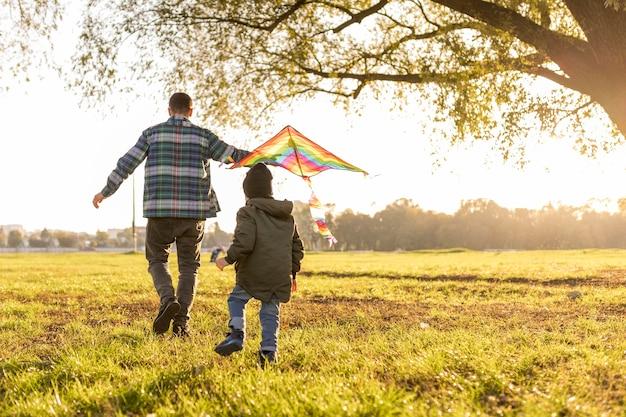 Pai e filho brincando com uma pipa longa vista