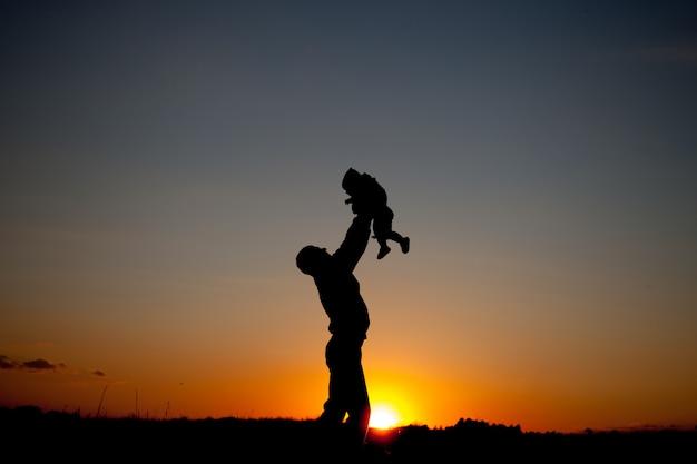 Pai e filho brincando na hora por do sol. conceito de família amigável.