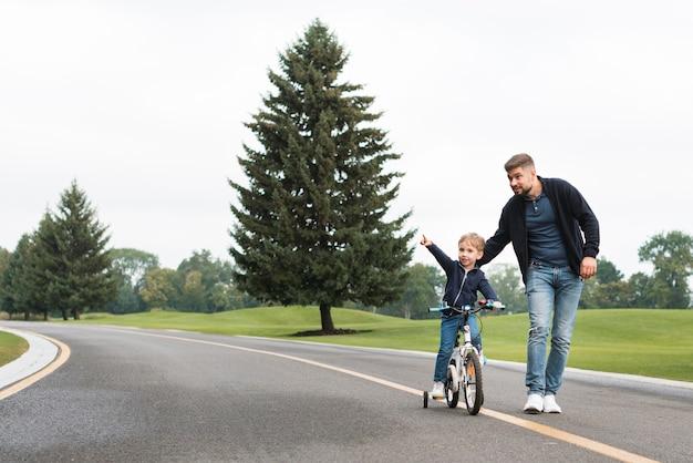 Pai e filho brincando no parque com uma bicicleta