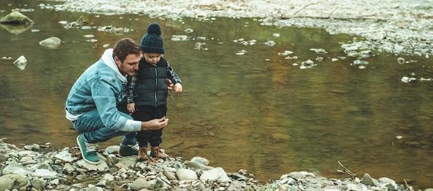 Pai e filho caminham e brincam juntos. o outono nas montanhas.