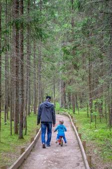 Pai e filho caminham na floresta. homem com menino ir no caminho.