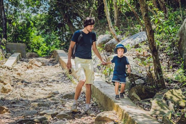 Pai e filho caminhando pela estrada da floresta