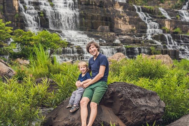 Pai e filho caminhantes, turistas na incrível cachoeira pongour é famosa e a mais bonita do outono