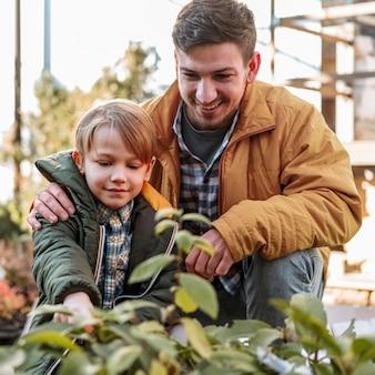 Pai e filho colhendo uma planta juntos