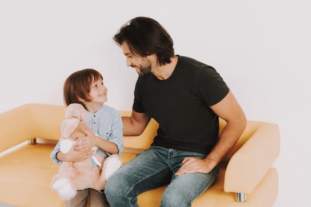 Pai e filho com bunny toy na sala de espera do médico.