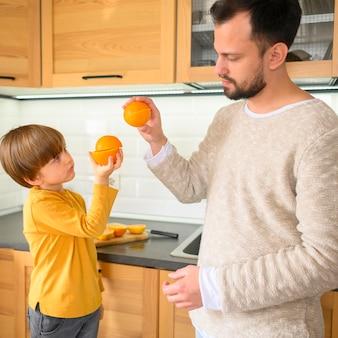 Pai e filho com cinco laranjas
