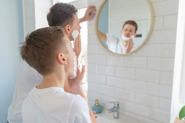 Pai e filho com creme de barbear por cima do ombro