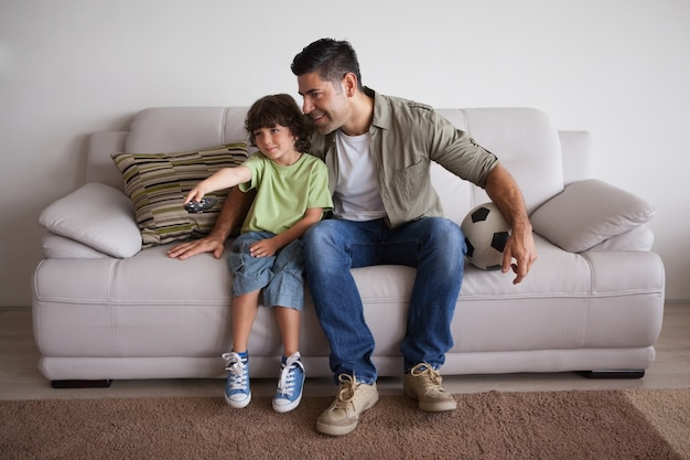 Pai e filho com futebol assistindo tv na sala de estar