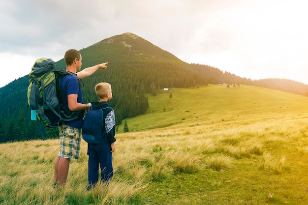 Pai e filho com mochilas, caminhadas juntos na montanha