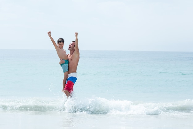 Pai e filho com os braços levantados desfrutando na praia