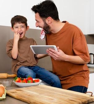 Pai e filho com tiro médio com tablet