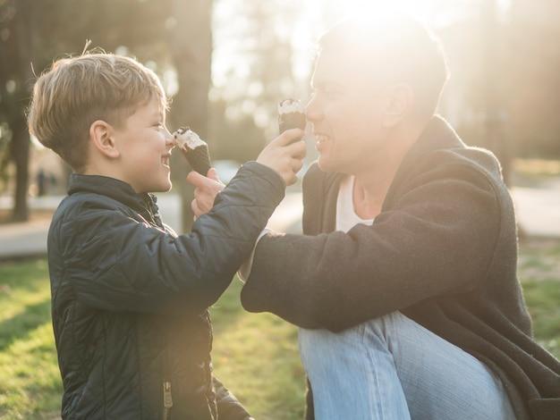 Pai e filho comendo sorvete plano médio