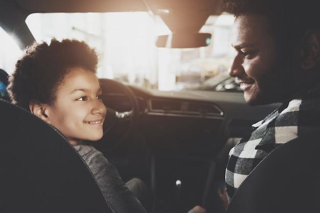 Pai e filho comprando carro sentado em assentos da frente.