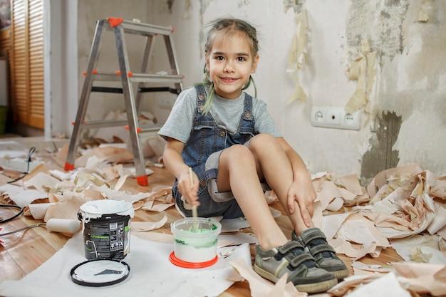 Pai e filho consertando o quarto juntos e pintando a parede juntos