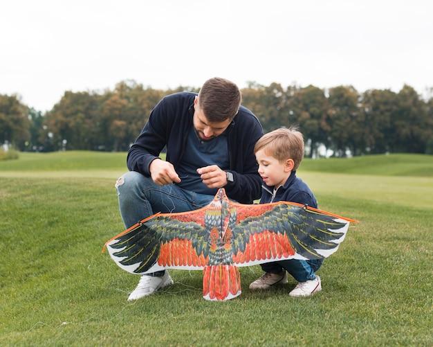 Pai e filho consertando uma pipa