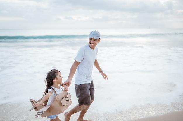Pai e filho correndo com um aviãozinho de papelão na praia