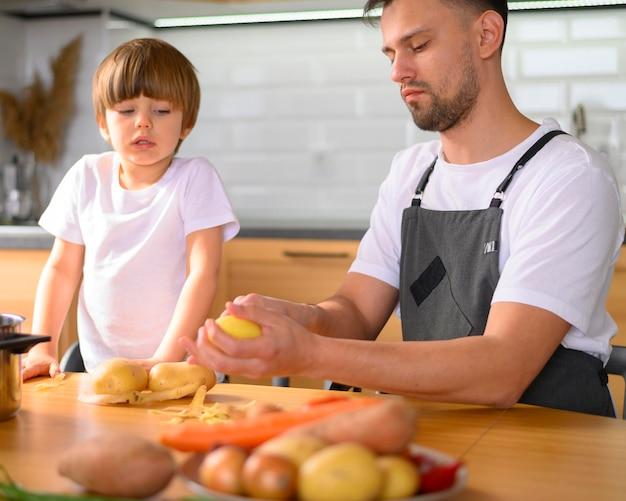 Pai e filho cortando os legumes