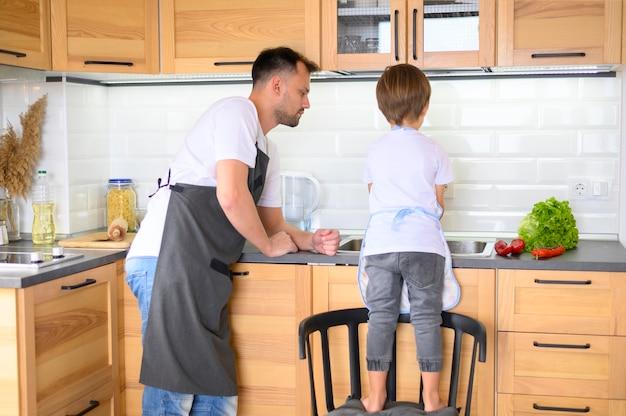Pai e filho cozinhando na cozinha vista longa