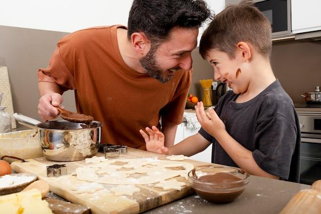 Pai e filho cozinhando tiro médio