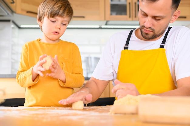 Pai e filho criando bolas de massa tiro médio