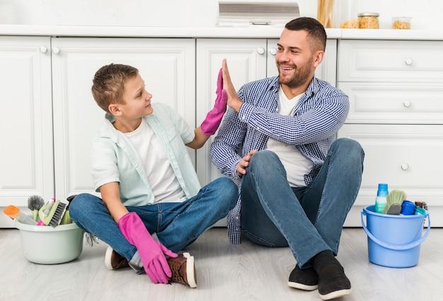 Pai e filho cumprimentando um ao outro durante a limpeza da casa