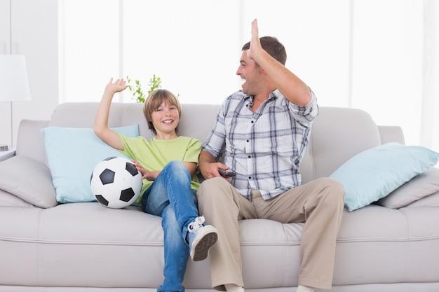 Pai e filho dando alta-cinco enquanto assistia partida de futebol