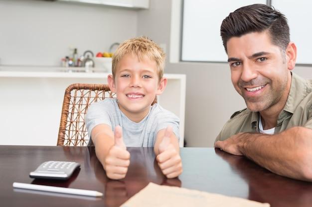 Pai e filho, dando o polegar para cima, sorrindo para a câmera na mesa