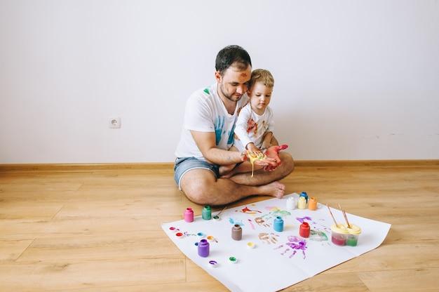 Pai e filho de cinco anos se divertindo pintura em casa