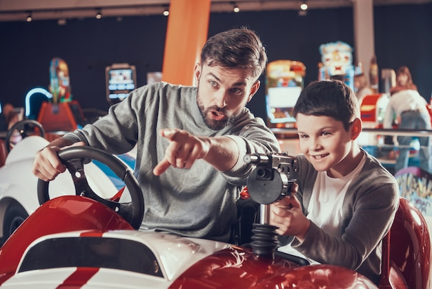 Pai e filho de joyfull que sentam-se no carro do brinquedo na alameda.