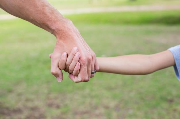 Pai e filho de mãos dadas no parque em um dia ensolarado