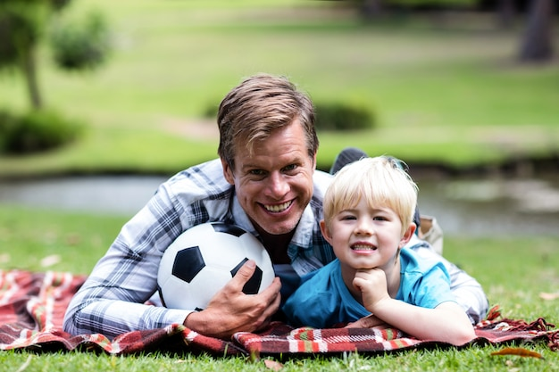 Pai e filho deitado no parque