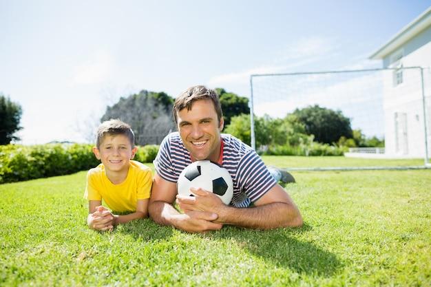 Pai e filho deitados na grama do parque em um dia ensolarado