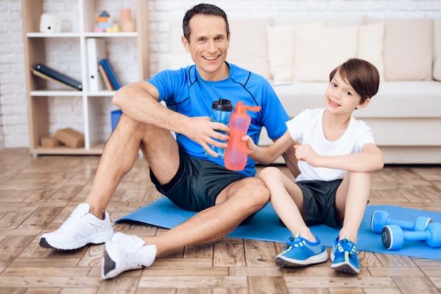 Pai e filho descansam após o exercício.