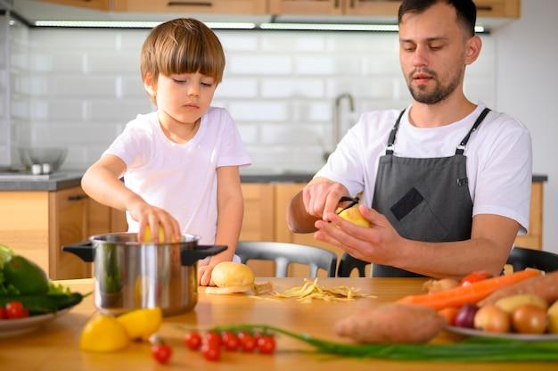 Pai e filho descascando legumes