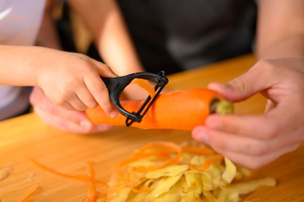 Pai e filho descascando um close-up de cenoura