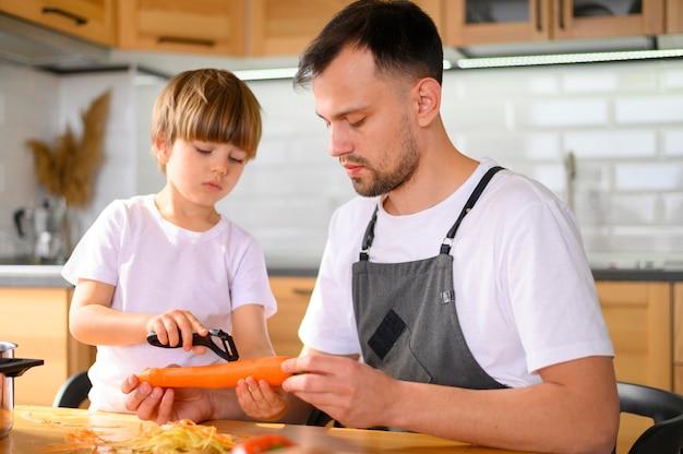 Pai e filho descascando uma cenoura