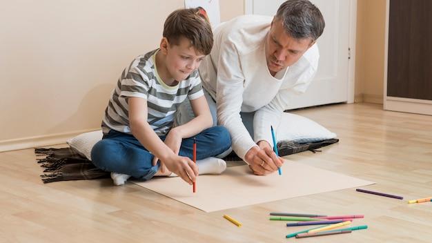 Pai e filho desenhando com marcadores