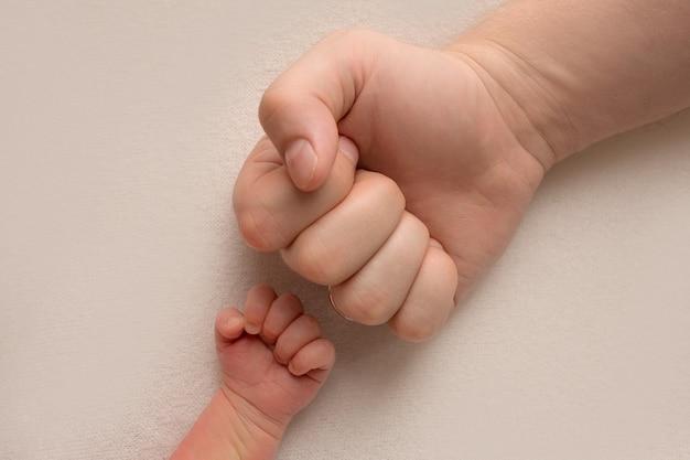 Pai e filho do menino bebê recém-nascido de mãos dadas na mesma pose, pequeno e grande punhos, foto preto e branco. foto de alta qualidade