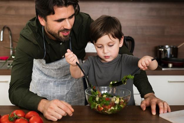 Pai e filho em casa fazendo salada