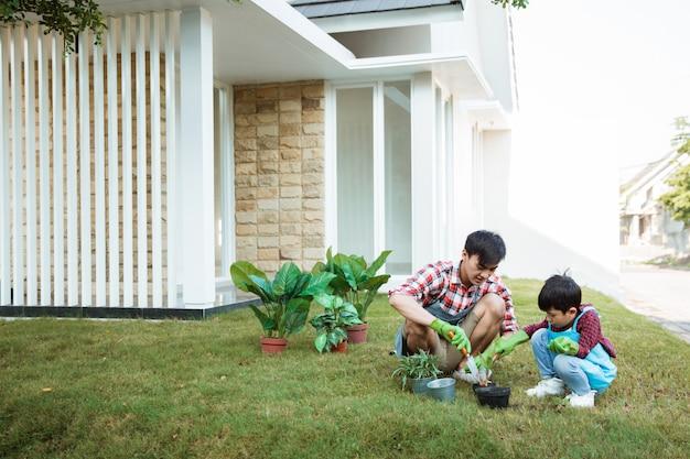 Pai e filho em casa jardinagem de manhã