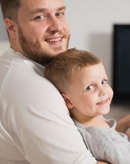Pai e filho em casa olhando para a câmera