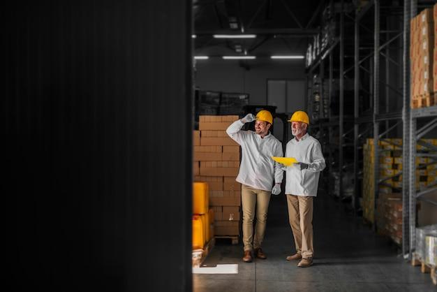 Pai e filho em pé no armazém com capacetes na cabeça e olhando para o pacote preparado para transporte. parecendo orgulhoso e satisfeito.