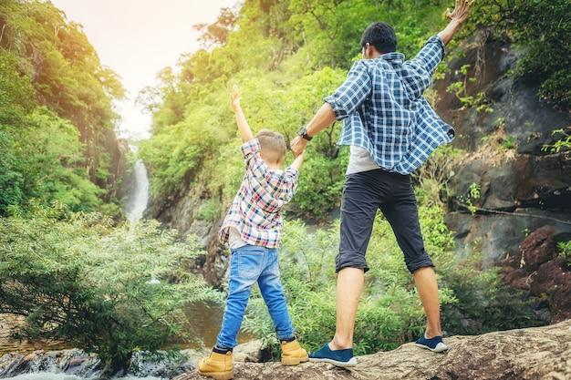 Pai e filho em pé viajam juntos e braços abertos comemoram suas férias com grande floresta
