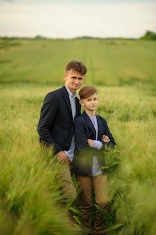 Pai e filho em um campo de trigo verde