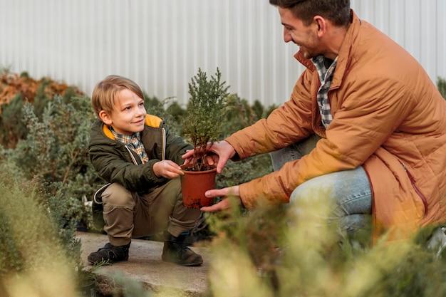 Pai e filho em um viveiro de árvores juntos