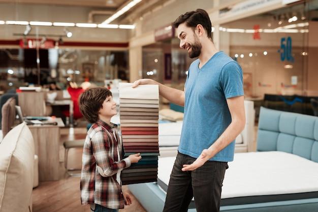 Pai e filho, escolhendo a cor das amostras de tecido
