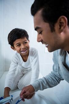 Pai e filho escovando os dentes no banheiro